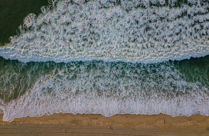 An Aerial View Of Tractor Lines In The Sand and Gorgeous Green Ocean Waves 7/3/20