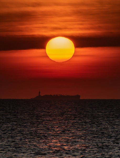 A Ship Passing In Front Of The Rising Sun 12/24/19