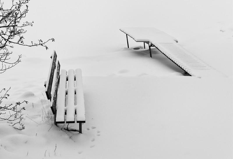 Vi har inte precis varit bortskämda med djup och knarrande djup snö den här vintern. I början av februari kom den i alla fall. Jag tog kameran och gav mig ut på fotoexkursion längs med vattnet i Varamon, Motala. Det är fascinerande att se en plats som på somrarna brukar vara helt proppfylld av soldyrkare helt öde. Det är som om man gick på en annan plats. Nu härskade det där kontemplativa lugnet, den där rytmen som liksom drar oss in i djupet av oss själva. Det är lyxtid.<br /> <br /> Rent fototekniskt är snö både en välsignelse och en utmaning. En välsignelse förstås för att natur klädd i snö kan bli så förbaskat vackert; det där rena uttrycket, naturliga gråskalor, spännande linjer…<br /> <br /> Utmaningen i att söka fotografera snö innebär att arbeta med fina valörer och att försöka arbeta med ett material som inte bara är en textur utan snarare hur många som helst. Snö ser som bekant aldrig likadan ut. Det ger en mycket speciell känsla att pulsa fram i fullständigt orörd snö. Skönhet är ordet som kommer för mig.<br /> <br /> Jag känner mig alltid som en upptäcktsresande på fototurer. Vem vet vad som dyker upp… Sinnena skärps, sensitiviteten stärks.