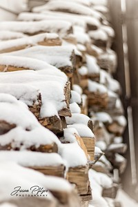 A stack of firewood resting under a layer of fresh snow. Enjoy and hold hands.