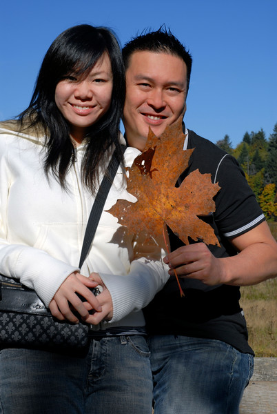 Two asian people hold up a large maple leaf on vacaction - tourism & travel in the great outdoors - lifestyle stock photo shot vertically<br /> <br /> The Nature Stock Photography Library features rights managed and royalty free wildlife, nature, travel stock photography and licenses for stock photos. We also sell high quality fine art nature prints and photo products. All images are by professional wildlife and nature photographer Christina Craft.