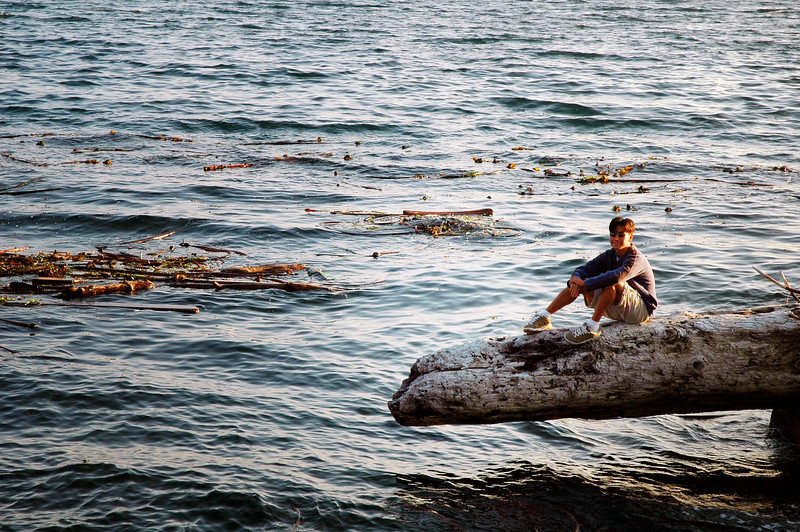 A healthy asian man sits on a log at the ocean shore<br /> <br /> <br /> <br /> Travel Stock Photography for the Nature Stock Photography Library by Professional Photographer Christina Craft