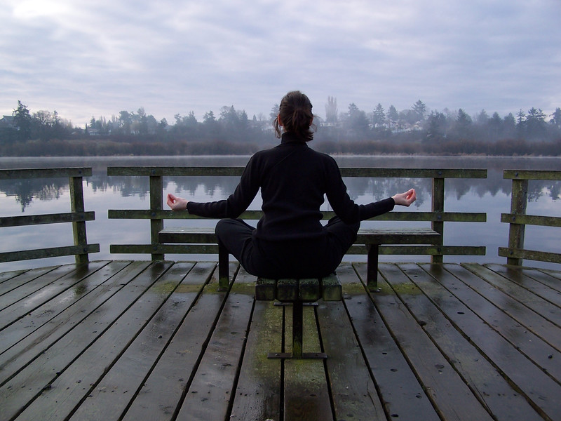 A young woman wearing a pony tail exercises and meditates by doing yoga on a dock in cottage country on a still lake with mist and fog<br /> <br /> Professional Nature Photography by Christina Craft of the Nature Stock Photography Library
