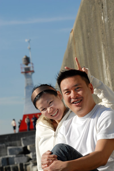 Two asian people enjoy the sunshine at a lighthouse <br /> <br /> The Nature Stock Photography Library features rights managed and royalty free wildlife, nature, travel stock photography and licenses for stock photos. We also sell high quality fine art nature prints and photo products. All images are by professional wildlife and nature photographer Christina Craft.