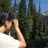 An asian man with binoculars looks into the woods and mountains in the wilderness