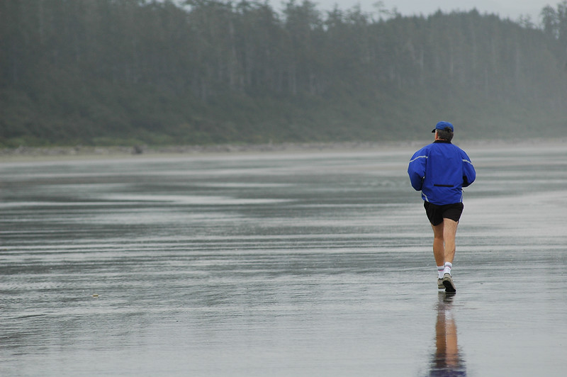 A man jogs along a beach at the ocean - Stock Photo by Nature Photographer Christina Craft