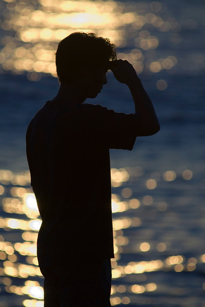 A man with his hand over his eyes looks out into the ocean at either sunrise or sunset along the coast