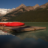 Red kayaks resting near lake louise in the rockies Rocky Mountain landscape mountains scenic landscape - Photograph by professional nature stock photographer Christina Craft