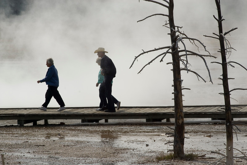 Tourists walk by a steaming geyser in Yellowstone National Park.