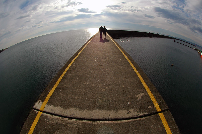 """I took this picture one of the first weeks I owned my new fisheye. The breakwater in Victoria has interesting geometry and I thought it looked cool to make the scene really round - so the people look like they're on top of the world. I've eventually turned this type of image into a """"gimmick"""" in my wedding photography"""" (see next image) and have honestly attracted so much business I can barely keep up. This type of image is also very impressive to stock photo agencies. It's original, but still simple."""
