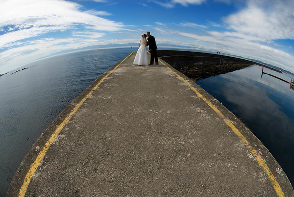 """This couple saw my photo of the people walking along the breakwater (with the fisheye) and asked if I could do it for their wedding photos. The results were better than I expected (the clouds added the perfect touch). I now have these images on my wedding website  <a href=""""http://www.christinacraft.com/wedding-photographer"""">http://www.christinacraft.com/wedding-photographer</a>) and have drummed up so much business for myself. All of my wedding marketing is based on this image - it's on my business card and I have a huge banner for tradeshows. It's like a calling card for my photography. It wasn't that hard to take... and it seems to set met a little bit apart from the competition (since it's so dramatically different from typical wedding photography)."""