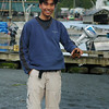 An asian man stands in a small fishing village holding a crab - Stock Photo by Nature Photographer Christina Craft