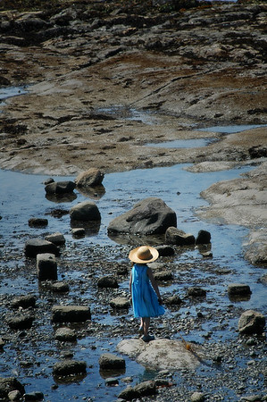A young girl wearing a blue dress and a sun hat at low tide