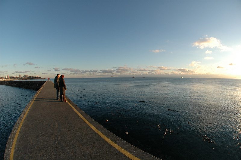 Wide angle lens of a breakwater at the ocean - two tourists - Nature Stock Image - Professional Nature Photography by Nature and Wildlife Photographer Christina Craft