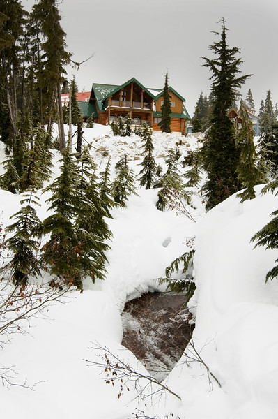 A winter scene featuring a chalet in the snow.