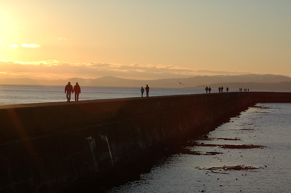 Breakwater sunset - silhouette of people walking down a seawall - Nature Stock Image - Professional Nature Photography by Nature and Wildlife Photographer Christina Craft