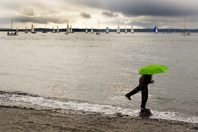 © Paul Conrad/Pablo Conrad Photography - A man balances on a rock while watching a regatta at Golden Gardens Park in Seattle, Wash.