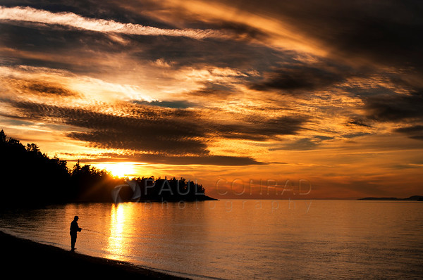 © Paul Conrad/Pablo Conrad Photography -  A fisherman tries his luck the Sun washes the sky orange as it sets west of Deception Pass on Whidbey Island north of Seattle, Wash.