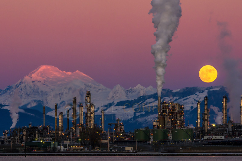 Wolf Moon Rising - The full Moon rises over the Tesoro refinery in Anacortes, Wash., as Mount Baker is bathed in the Sun's last rays on Wednesday evening Jan. 11, 2017. (© Paul Conrad/Paul Conrad Photography)