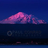 © Paul Conrad/Pablo Conrad Photography  The last rays of the setting Sun bathes the snow-capped peak of Mount Baker in alpenglow as the lights of the city of Bellingham, Wash., begin to turn on during evening April 23, 2013.
