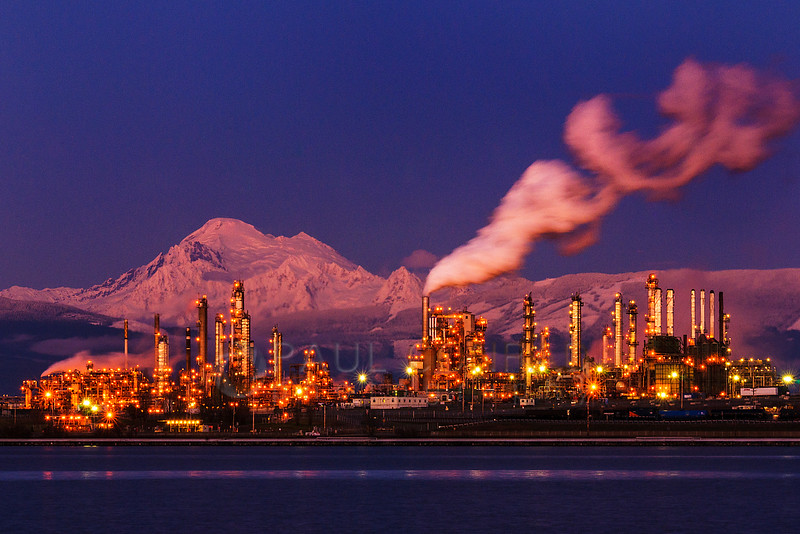 Mt. Baker & Tesoro Refinery - Mount Baker is bathed in the rays of the setting Sun a the lights of the Tesoro Anacortes refinery begin to illuminate on Friday afternoon Jan. 31, 2014, in Anacortes, Wash. (© Paul Conrad/Paul Conrad Photography)