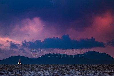 © Paul Conrad/Pablo Conrad Photography - A lone sailboat bounds the waves during sunset at Locust Beach in Bellingham, Wash., on Saturday Jan. 14, 2012.
