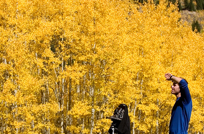 "Paul Conrad/The Aspen Times Surrounded on all sides by peaking aspens, Jason Manke of Boulder attempts to choose his angle while photographing the colors along Castle Creek Road Sunday morning September 25, 2005. ""They're awesome,"" he said, ""this road is beautiful. I've shot enough to consider the possibility of doing (photography) professionally."""