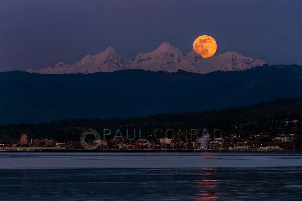 Full Pink Supermoon Over Twin Sisters - The full pink supermoon rises over the Twin Sisters and Bellingham on Tuesday evening April 7, 2020, as seen from Lummi Shore Drive and Cagey Road in Whatcom County, Wash.