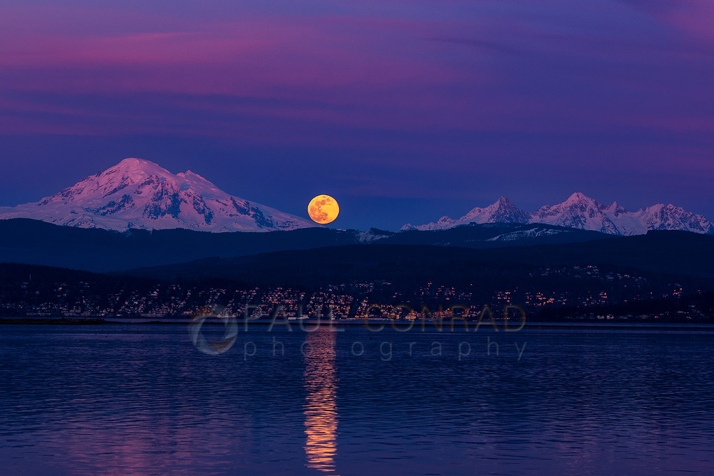 Super Worm Moon - The Super Worm Moon rises over Bellinhgam, Wash., between Mount Baker and the Twin Sisters during the first day of spring on Wednesday evening March 20, 2019, as seen from the south end of Lummi Shore Drive. (photo © Paul Conrad/Paul Conrad Photography)