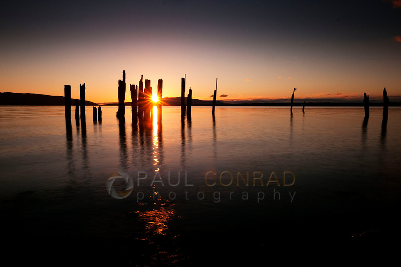 © Paul Conrad/Pablo Conrad Photography  The setting Sun creates a starburst between two pilings on Locust Beach in Bellingham, Wash.