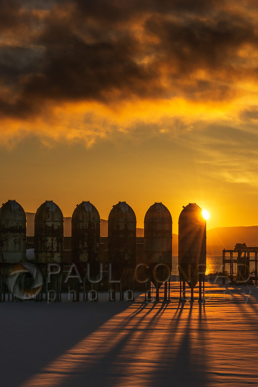 Setting Sun behind Georgia Pacific digesters - The setting Sun peeks from behind the Georgia Pacific paper mill digesters on a crisp cold evening in Bellingham, Wash. (© Paul Conrad/Paul Conrad Photography)