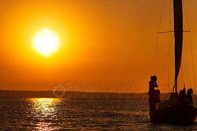 © Paul Conrad/Pablo Conrad Photography - People on a sailboat enjoy the setting Sun over Bellingham Bay in Bellingham, Wash., on Saturday evening July 8, 2012.