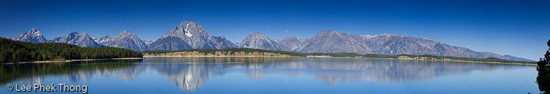 Panoramic view of the reflections of the Teton Range on Jackson Lake