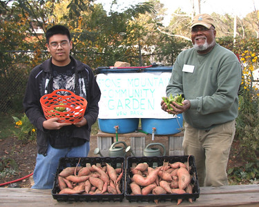 Giovanny Campa, left, and Columbus Brown stand in the food pantry section of the Stone Mountain Community Garden with some of the vegetables grown in the garden. Over 1400 pounds of fresh produce was grown in the garden during 2012. (Photo Courtesy of Columbus Brown)