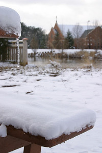 A single icicle hangs from a picnic table on the grounds of St. George Village, Roswell, as the snow-topped roof of St. Peter Chanel Church looms in the background. Afternoon temperatures started to push upward and a slow meltdown ensued Feb. 13, following the previous day's snowfall that left 3-6 inches around the metropolitan Atlanta area.