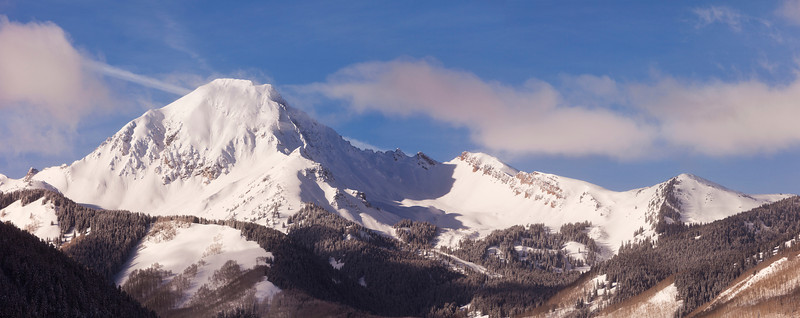 A winter landscape in the Elk Mountains of Colorado with a view of the snow-covered Mt. Daly, a mountain that is over 14,000 feet tall.