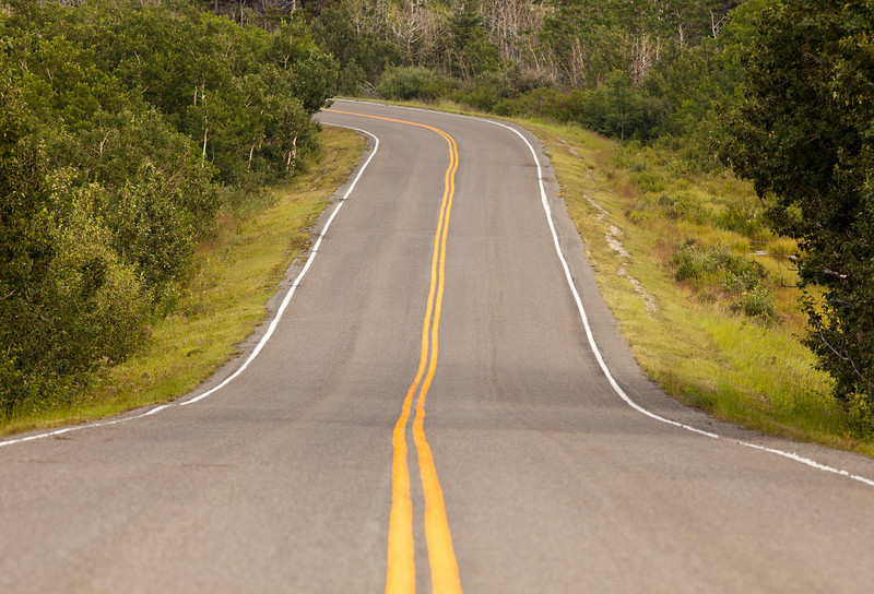 An open stretch of two-lane highway in Glacier National Park. The lines lead into the distance and then around a turn.
