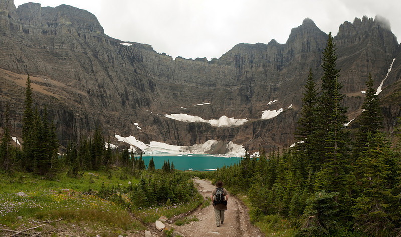 One hiker walking towards Iceberg Lake in Glacier National Park. The headwall of the valley is a perfect bowl formed by cliffs with hanging glaciers; the ice calves off to form icebergs in the lake.