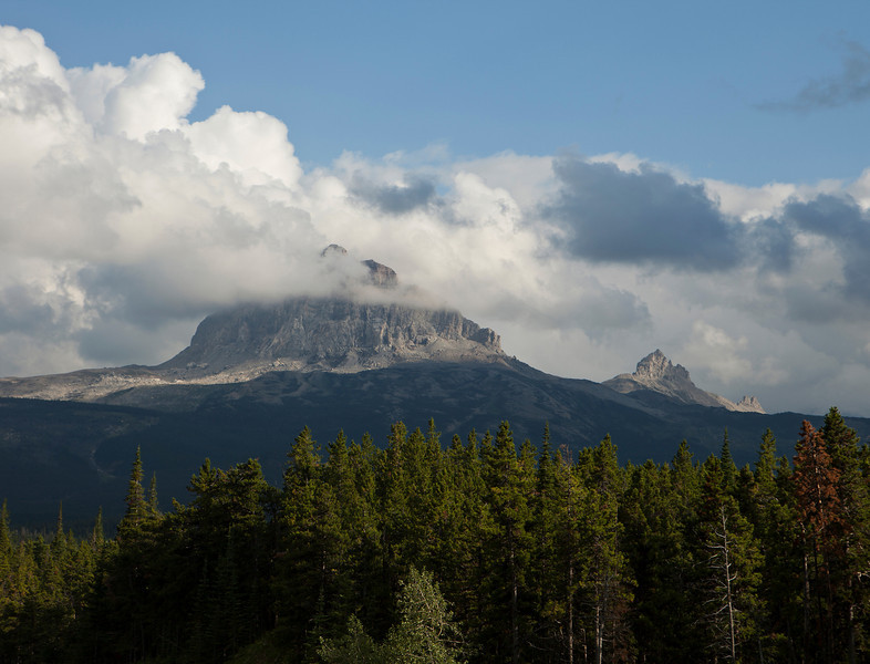 Big Chief Mountain in Glacier National Park on a day when it is surrounded by a halo of clouds. The mountain is a granite monolith that rises by itself in a corner of the park.