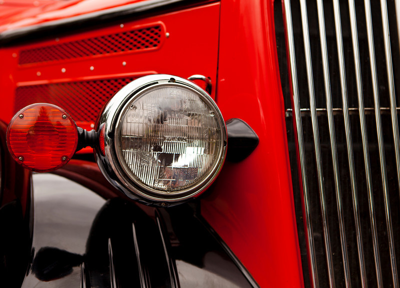 A front headlight detail on one of the grand old red buses from Ford at Glacier National Park.