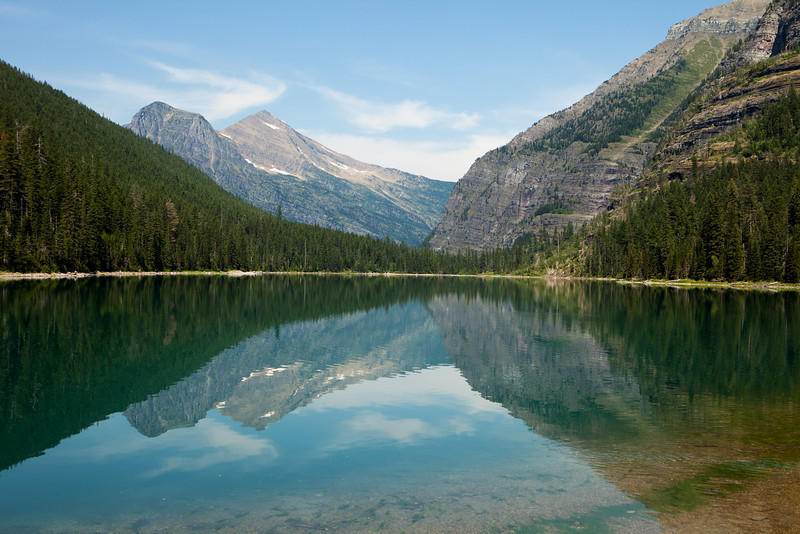 Landscape of Avalanche Lake and nearby mountains in Glacier National Park. The reflection on the lake provides a near mirror image.