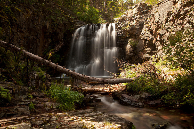 Scenic view of Lower Twin Falls in Glacier National Park with the waterfall set between the rock walls of the stream bed. A long exposure smooths the water and shows the full shape of the falls.