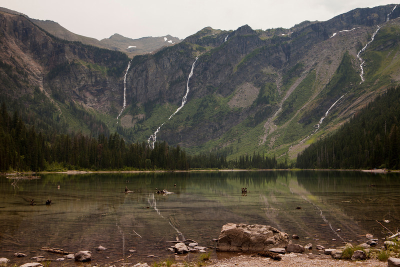 Avalanche Lake in Glacier National Park. The headwall of the valley is in the background with several waterfalls that are cascading down the cliffs from glaciers above.