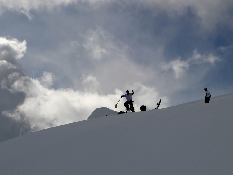 A group of snowboarders, outlined against the sky, who were building a jump on a slope high up on Mt. Rainier -- out of bounds for most skiers.