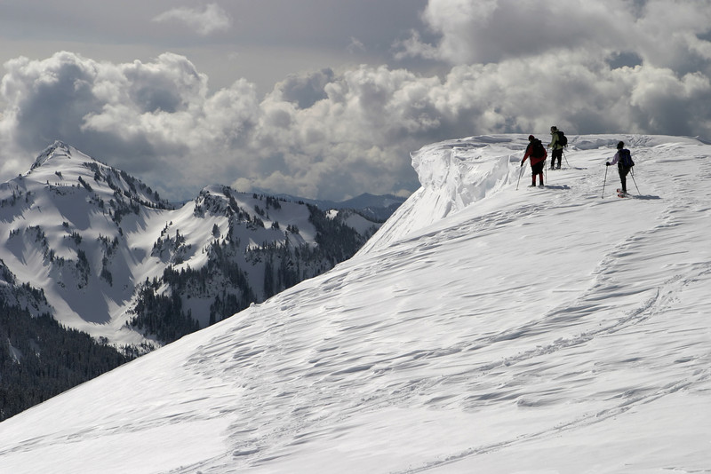 Three climbers exploring the edge of an ice cornice on Mt. Rainier. This was a dangerous exploit as the lips of these cornices can be very unstable.
