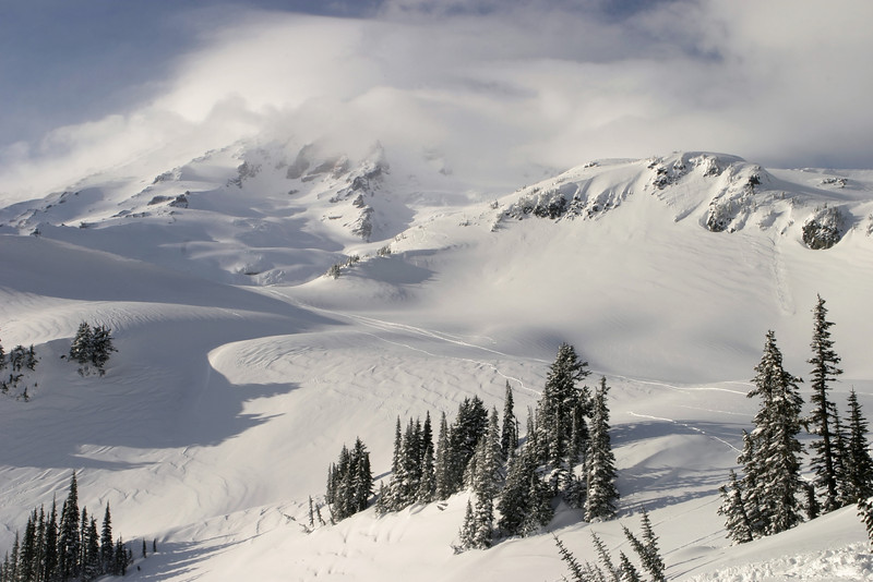 A view of the Mt. Rainier summit on a day when the summit was alternately bathed in the sun and covered in clouds.