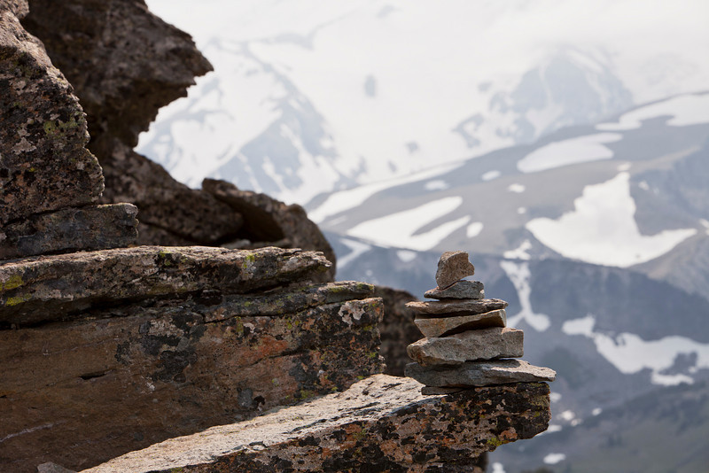An organized pile of rocks is stacked up to form a small cairn or trail marker on a ledge high up on Mt. Rainier. In the background, the glaciers on the mountain fade into the distance.