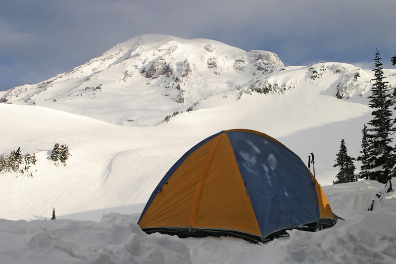 A colorful tent located at 6,000 feet up on Mount Rainier. This is an unusual winter image of the mountain since it was taken in sunlight with light clouds drifting over the summit. This would be a typical starting off point for an expedition to climb up the mountain.