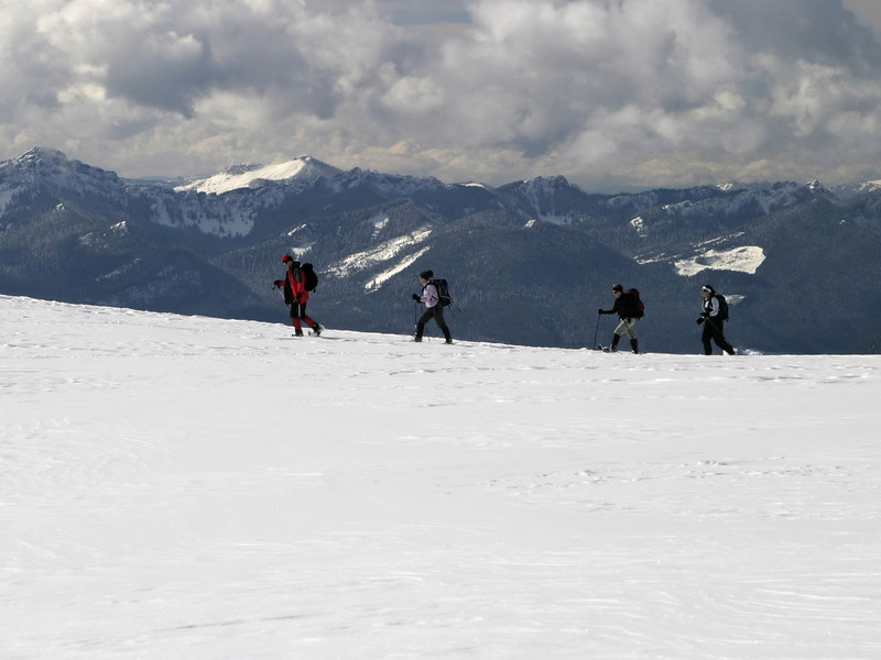 A group of climbers trekking along a ridge high up on the side of Mt. Rainier. The Cascade Mountain range is in the background.