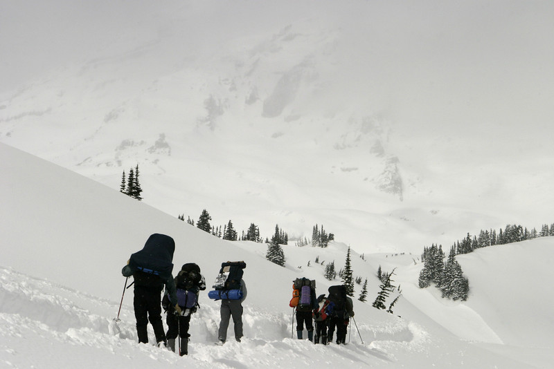 A group of mountain climbers ascending Mt. Rainier into the midst of a storm. The summit peak dead ahead is covered in clouds.